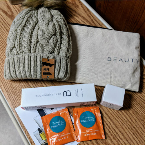 small white rectangular and square boxes, hand lotion, lip balm, orange foil tea bags, khaki knit winter hat with furry pom pom, cream zippered canvas pouch, says BEAUTY
