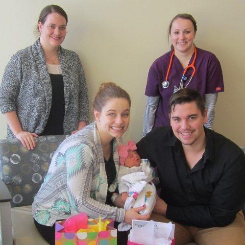 Parents holding a newborn.