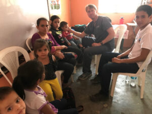 Children are sitting in chairs to see a male doctor in Honduras.